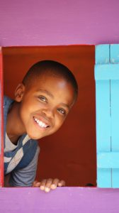 young boy smiling from the window of a playhouse