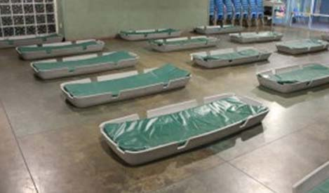 empty beds laid out inside a shelter
