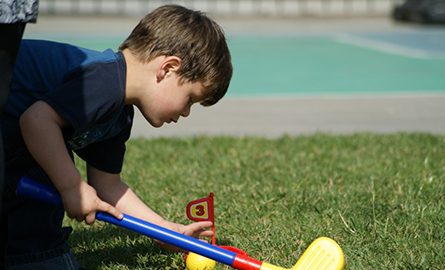 little boy setting a flag from a toy golf set